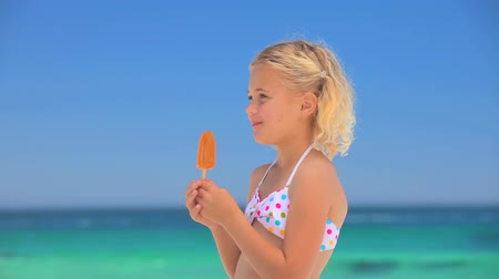 dondurma : Little blonde girl eating a water ice standing on a beach Stok Video