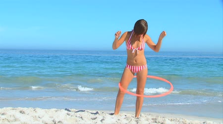 abroncs : Attractive woman standing on a beach playing with a hoop
