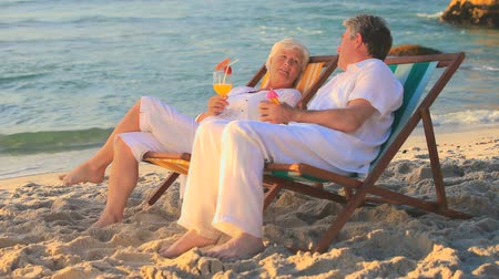 caucasiano : Mature couple talking sitting in deckchairs on a beach