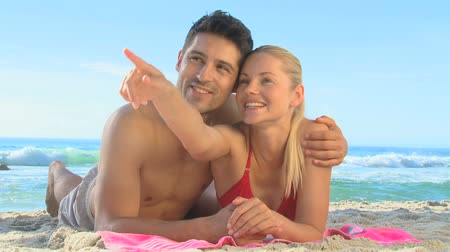 casal heterossexual : Cute couple hugging and waving while lying on a beach