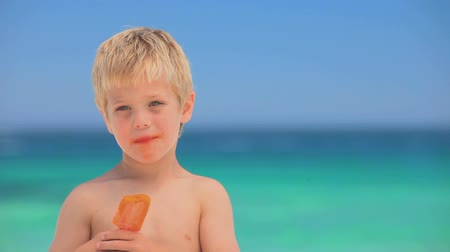 menő : Happy little blond boy eating a water ice on the beach