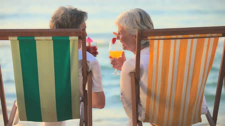 emekli : Elderly couple sitting in their deck chairs on a beach drinking cocktails
