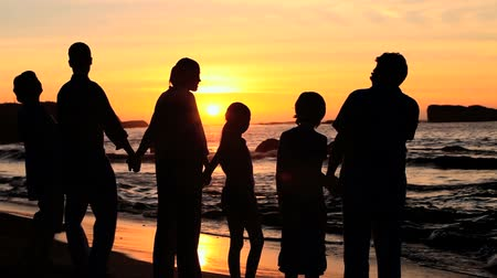 erkek güzellik : Family holding hands at the waters edge at sunset