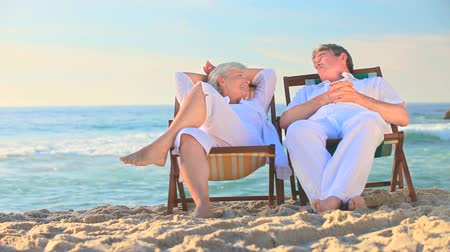 kumlu : Elderly couple sitting in deckchairs on a beach with their backs to the sea