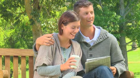 palavras cruzadas : Young couple doing crosswords while sitting on a bench in the park Stock Footage