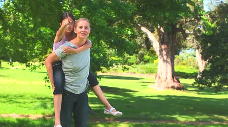 bonitinho : Young woman playing with her daughter in the park Stock Footage