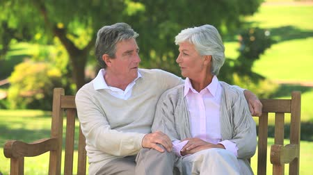 emekli : Mature couple talking while sitting on a bench in the park