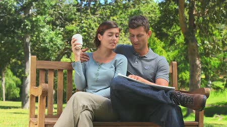 palavras cruzadas : Young couple looking at a newspaper in the park Stock Footage
