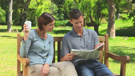 palavras cruzadas : Young couple chatting and reading a newspaper in the park Stock Footage