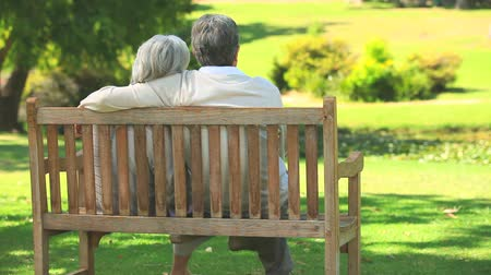 spojrzenie : Mature couple sitting talking on a bench in the park