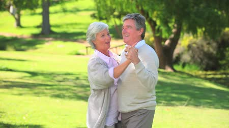 emekli : Mature happy couple having fun dancing in the park Stok Video