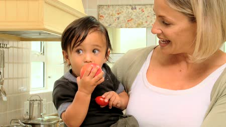 két : Mother in kitchen holding baby with red apple