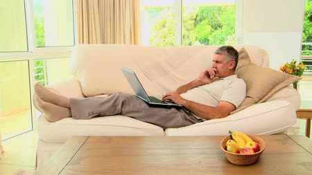 eyes closed : Man lying on sofa excited about something on laptop