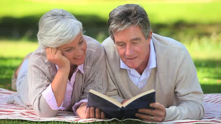 spojrzenie : Mature couple reading a book while lying on the grass in the park