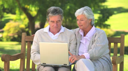 smích : Mature couple surfing on their laptop while sitting on a bench in the park
