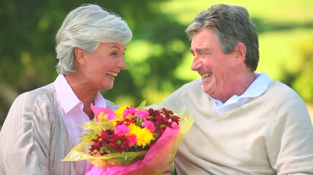 amadurecer : Elderly couple holding a bunch of flowers while sitting on a bench in the park Stock Footage