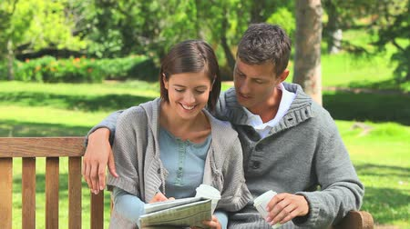 palavras cruzadas : Young couple doing crosswords and drinking coffee in the park Stock Footage
