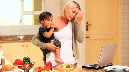 prole : Woman in kitchen coping with baby and laptop and phone