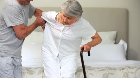 cidadão idoso : Middleaged man helping his wife to stand up in the bedroom