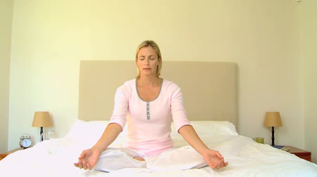 posição : Blonde young woman sitting on a bed in the lotus position doing metitation