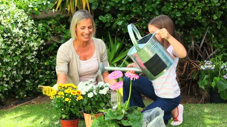 günler : Mother helping her daughter to water potted plants in the garden Stok Video