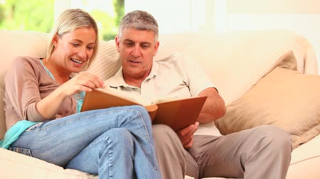 tome : Attractive couple looking at an album while sitting on the sofa Stock Footage