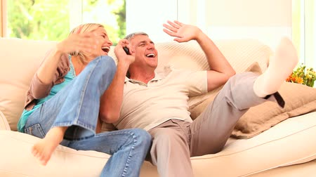 assistindo : Very happy couple watching sports on tv in the living room