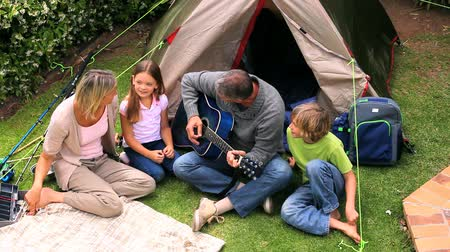 kamp : Father playing guitar in front of his family in the garden Stok Video