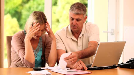 banknoty : Woman in despair about bills with husband trying to help Wideo