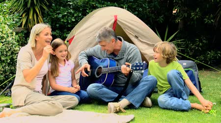 kamp : Family singing together while the father is playing guitar in garden Stok Video