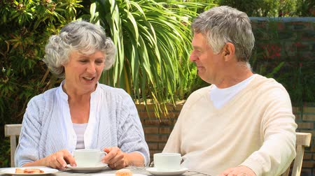 гражданин : Mature couple chatting and drinking coffee in their garden