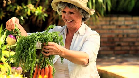 бабушка : Mature woman proudly showing selected root vegetables Стоковые видеозаписи