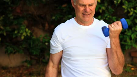 amadurecer : Mature man outdoors exercising his arms with dumbbells Stock Footage