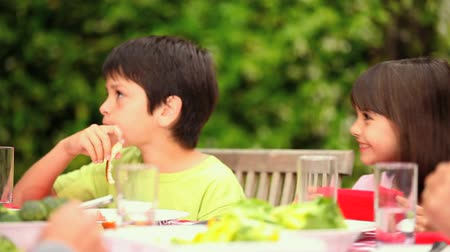 sağlıklı beslenme : Children sitting at a garden table chatting and enjoying lunch