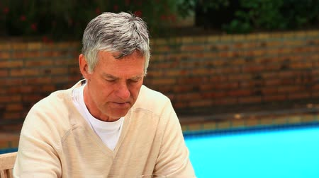 positive ageing : Man sitting by a swimming pool tasting a glass of red wine