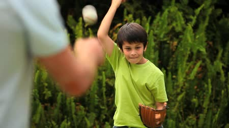 juventude : Young boy playing baseball with his father in the garden