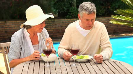 hareketli : Mature couple sitting at a table by a swimming pool having a meal with wine Stok Video