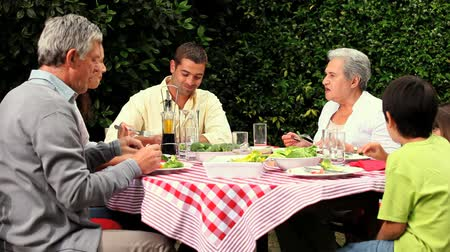 genç çift : Children having lunch in the garden with their parents and grandparents