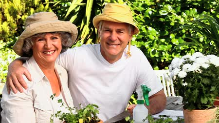 amadurecer : Mature couple wearing sunhats posing for a photo in the garden
