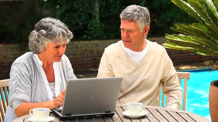 amadurecer : Mature couple sitting at a table by a swimming pool using a laptop