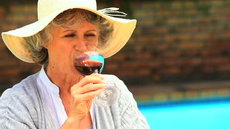 positive ageing : Woman tasting red wine sitting by a swimming pool