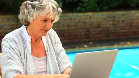 amadurecer : Mature woman using a laptop sitting by a swimming pool Stock Footage