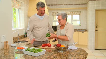 salad : Mature couple cooking together in the kitchen