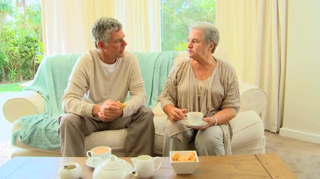 keksz : Mature couple sitting having tea and biscuits and a chat