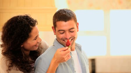 taunting : Woman laughing and taunting her boyfriend with a strawberry