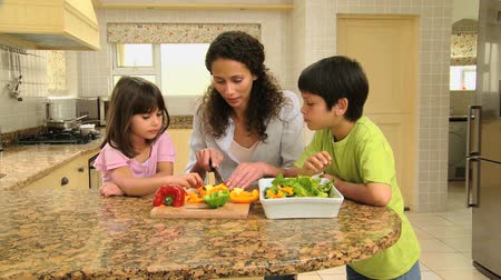 gotowanie : Children helping mother to cook and eating raw peppers Wideo