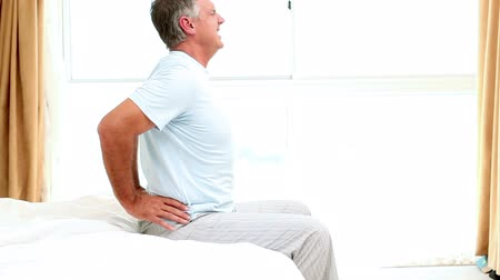 painéis : Side view of mature man experiencing back pain on the edge of his bed Stock Footage