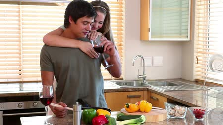 namorado : A man cooking and drinking wine while his wife embrace him