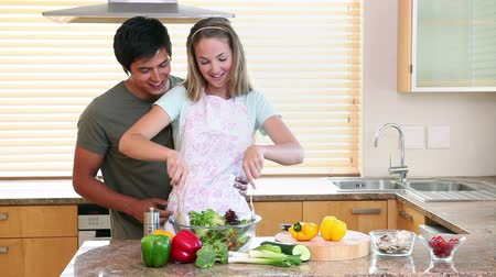 kötény : A woman mixing a salad while a man comes to embrace her