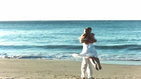 ragaszkodás : Man holding his girlfriend on the beach in slow motion